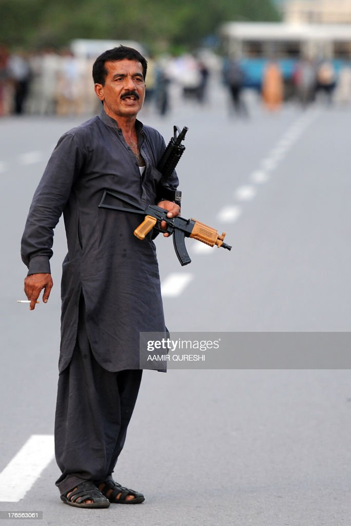 A Pakistani gunman holds his guns as he smokes a cigarette during a standoff with police in Islamabad on August 15, 2013. Police in Pakistan capital Islamabad arrested late on August 15 a man armed with two automatic guns after more than five hours of a standoff, police said. The gunman was shot in the legs by police commandoes after a negotiator jumped over the gunman to disarm him during talks, but the gunman tried to escape and opened fire. The gunman, who had been travelling in a car with a woman and two young children, was earlier stopped for a traffic violation, police said.