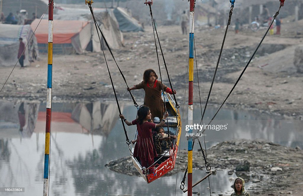 Pakistani gypsy children enjoy aplaying on a swing near their makeshift tents in Lahore on January 31, 2013. Year-on-year inflation stood at 6.9 percent in November, the State Bank of Pakistan said in a statement, a faster fall than had been estimated. Food inflation dropped to 5.3 percent and non-food inflation to 8.1 percent. AFP PHOTO/Arif ALI