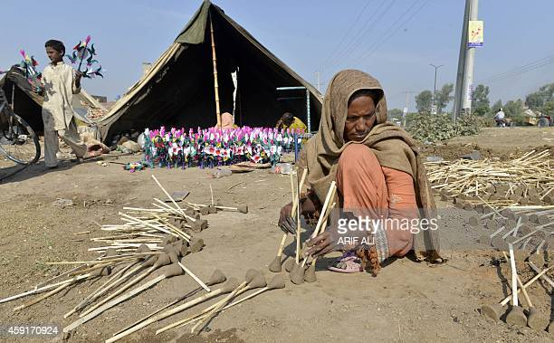 A Pakistani gypsy woman mades artificial flowers outside her makeshift home in Lahore on November 18 2014 Pakistan was granted a USD68 billion IMF...