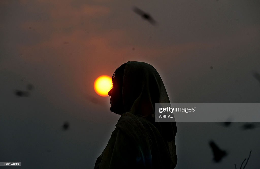 A Pakistani gypsy woman walks during sunset in Lahore on January 31, 2013. Year-on-year inflation stood at 6.9 percent in November, the State Bank of Pakistan said in a statement, a faster fall than had been estimated. Food inflation dropped to 5.3 percent and non-food inflation to 8.1 percent. AFP PHOTO/Arif ALI