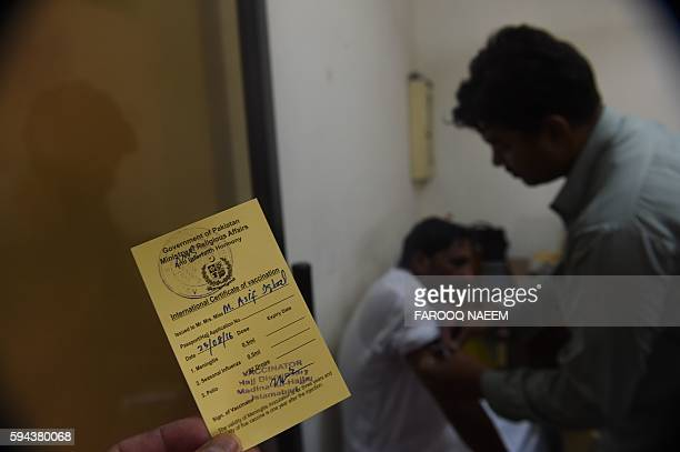 A Pakistani Hajj pilgrim is vaccinated by a paramedic at The Hajj Complex in Islamabad on August 23 before leaving for the annual Hajj pilgrimage to...