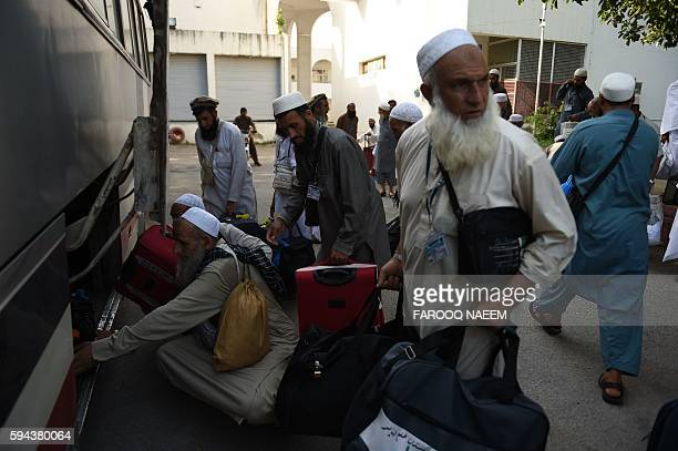 Pakistani Hajj pilgrims oad their luggage onto a waiting bus at The Hajj Complex in Islamabad on August 23 before leaving for the annual Hajj...