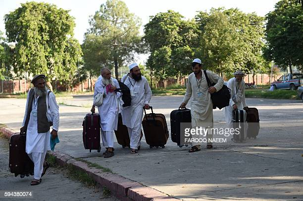 Pakistani Hajj pilgrims walk towards waiting transport at The Hajj Complex in Islamabad on August 23 before leaving for the annual Hajj pilgrimage to...