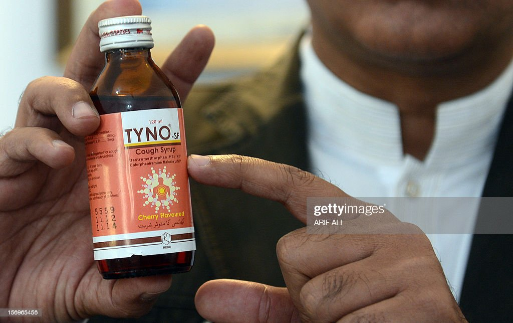 A Pakistani health official holds a bottle of toxic cough syrup at a hospital in Lahore on November 26, 2012. At least 16 people have died after drinking a toxic cough syrup in the Pakistani city of Lahore, forcing authorities to close three pharmacies and a medicine factory, officials said. AFP PHOTO/Arif ALI