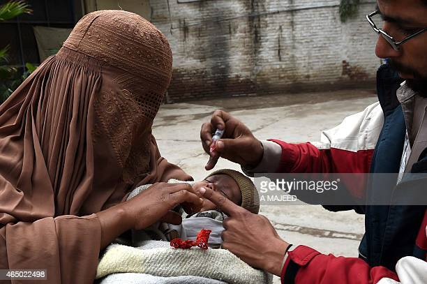 A Pakistani health worker administers polio drops to a child during a polio vaccination campaign in Peshawar on March 3 2015 Police in northwest...