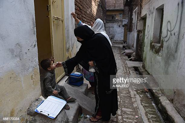 A Pakistani health worker administers polio drops to a child during a polio vaccination campaign in Peshawar on September 14 2015 Pakistan is one of...