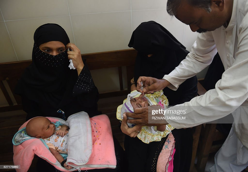 A Pakistani health worker administers polio vaccine drops to a child during a polio campaign in Karachi on May 2, 2016. Pakistan is one of only three countries in the world where polio remains endemic but years of efforts to stamp it out have been badly hit by reluctance from parents, opposition from militants and attacks on immunisation teams. / AFP / RIZWAN
