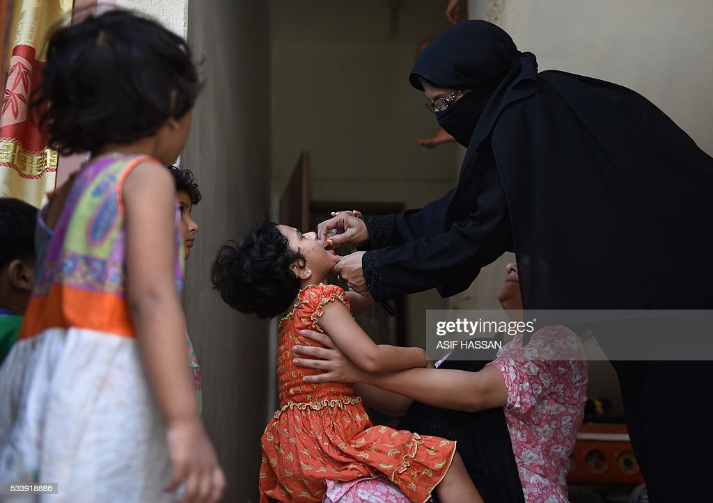 A Pakistani health worker administers polio vaccine drops to a child during a door-to-door polio campaign in Karachi on May 24, 2016. Pakistan is one of only three countries in the world where polio remains endemic but years of efforts to stamp it out have been badly hit by reluctance from parents, opposition from militants and attacks on immunisation teams. / AFP / ASIF