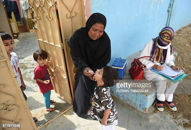 A Pakistani health worker administers polio vaccine drops to a child during a doortodoor polio campaign in Karachi on October 24 2016 Pakistan is one...