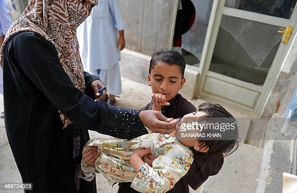 A Pakistani health worker administers polio vaccine drops to a young girl in Quetta on May 12 2014 Pakistan will set up mandatory immunisation points...