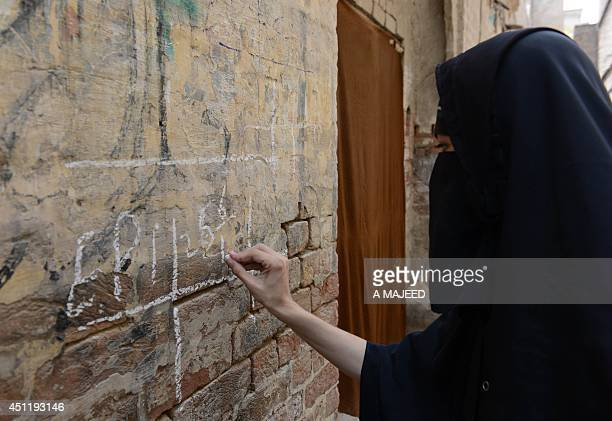 A Pakistani health worker writes a note over the wall of a residence after vaccinating children during a polio drive in Bannu on June 25 2014...