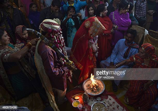A Pakistani Hindu couple performs a Hindu ritual during a mass wedding ceremony in Karachi on January 2 2015 Some 50 Hindu couples participated in...
