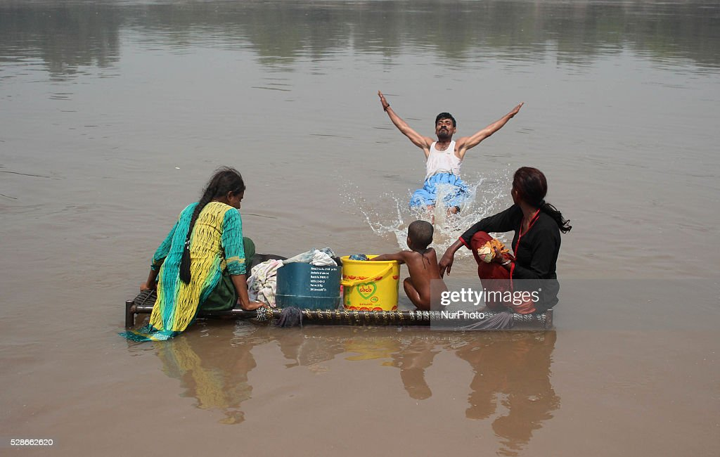 Pakistani homeless family sits on local bed (charpai) for cool themselves in ravi river at Lahore, Pakistan on May 06, 2016.