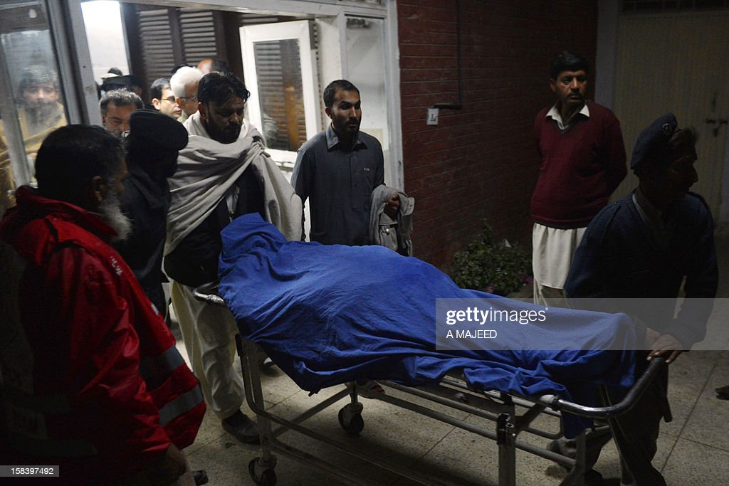 Pakistani hospital employee carry the body of a victim on a stretcher at a hospital after a rocket attack on an airport in Peshawar on December 15, 2012. Militants fired rockets into the airport of Pakistan's northwestern city Peshawar late on Saturday, killing four people, wounding dozens more and forcing the airport to close, officials said.