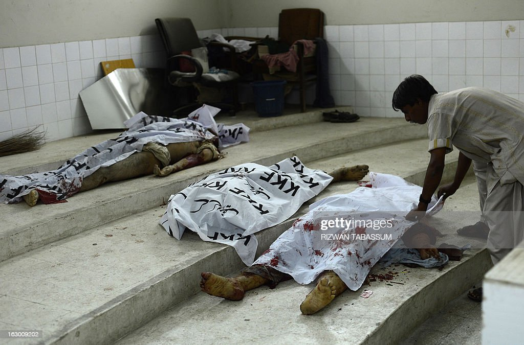 A Pakistani hospital employee covers the dead body of a bomb blast victim in Karachi on March 3, 2013. A bomb attack in Pakistan's largest city Karachi on Sunday killed at least 23 people, including women and children, and wounded 50 others, police said. AFP PHOTO/Rizwan TABASSUM