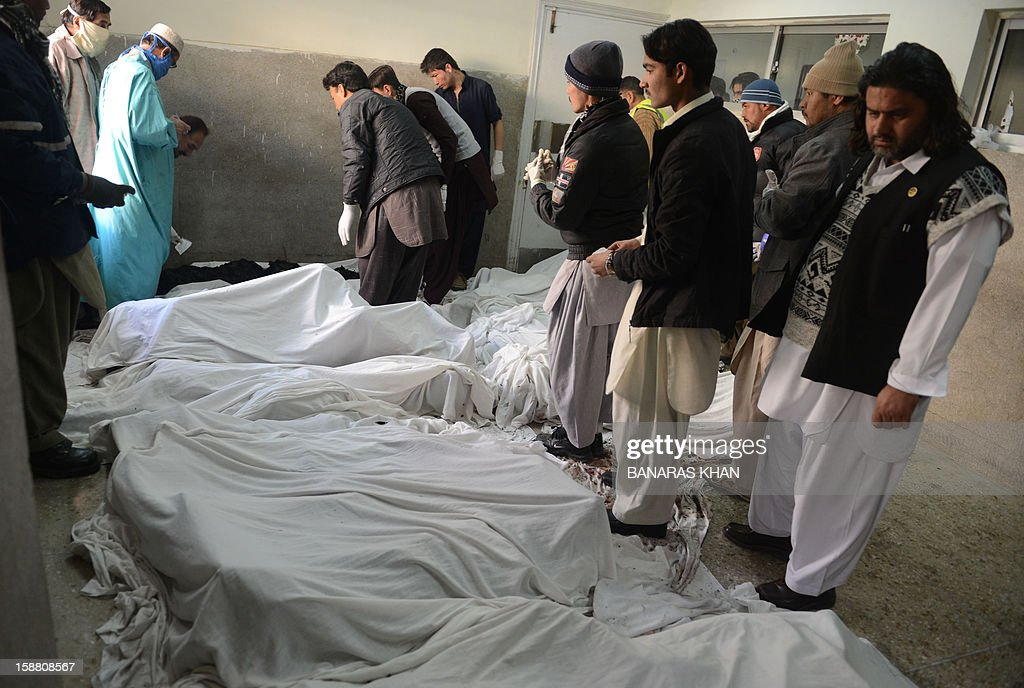 Pakistani hospital staff members put identification clips onto the bodies of Shiite pilgrims in Quetta on December 30, 2012. A car bomb attack on buses carrying Shiite Muslim pilgrims to Iran killed 19 people and injured 25 in Pakistan's insurgency-hit southwest on December 30, officials said.