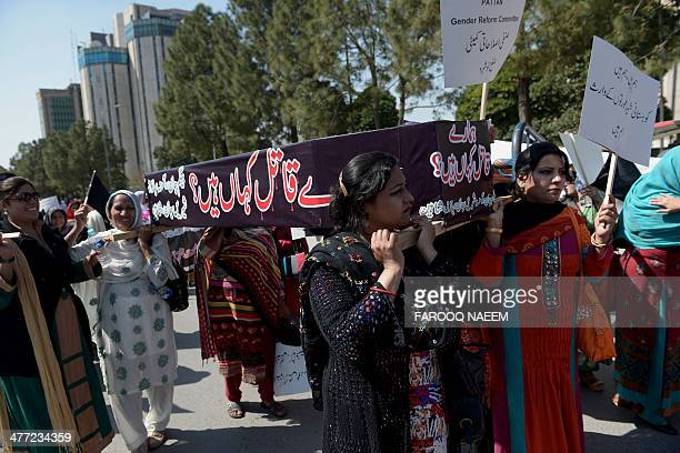 Pakistani human rights activists carry a coffin symbolising honour killing as they take part in a protest on International Women's Day in Islamabad...