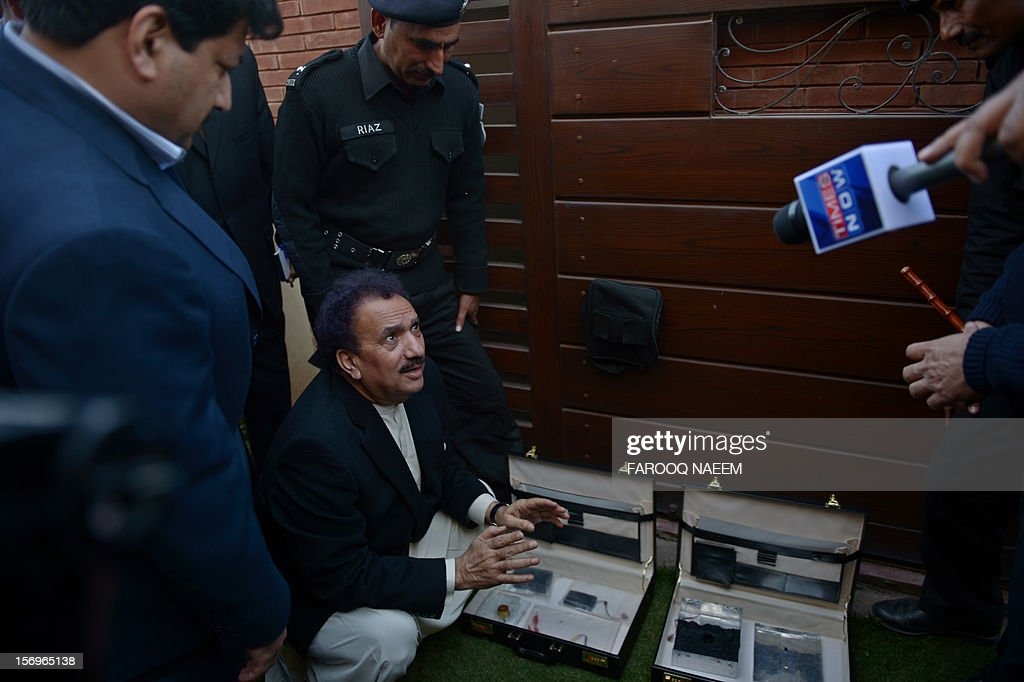 Pakistani Interior Minister Rehman Malik (C) inspects the bomb planted device as journalist and television anchor Hamid Mir (L) looks on in Islamabad on November 26, 2012. Mir, a high-profile Pakistani journalist and television anchor escaped an assassination bid on Monday when police defused a bomb planted under his car in Islamabad, police and his channel said. AFP PHOTO/Farooq NAEEM