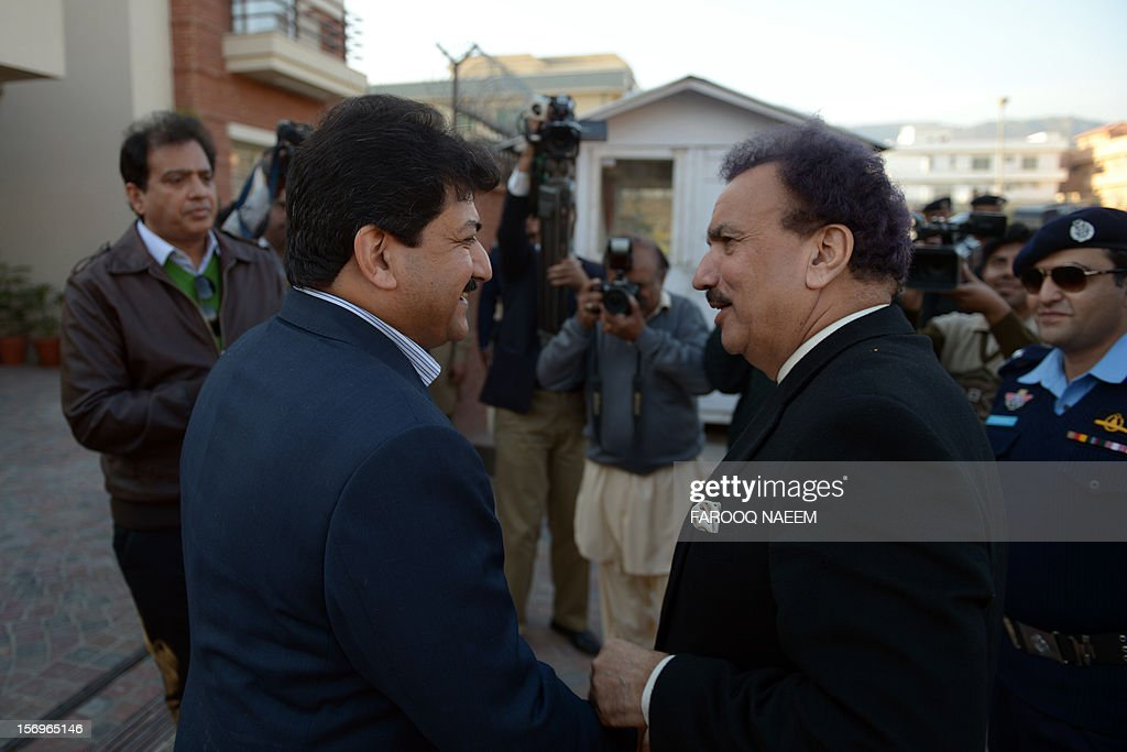 Pakistani Interior Minister Rehman Malik speaks with journalist and television anchor, Hamid Mir upon arrival at his home in Islamabad on November 26, 2012. Mir, a high-profile Pakistani journalist and television anchor escaped an assassination bid on Monday when police defused a bomb planted under his car in Islamabad, police and his channel said. AFP PHOTO/Farooq NAEEM