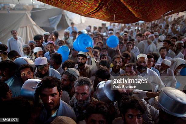 Pakistani internally displaced push and shove to get food for dinner at the Chota Lahore relief camp housing thousands of people May 29 2009 in Swabi...