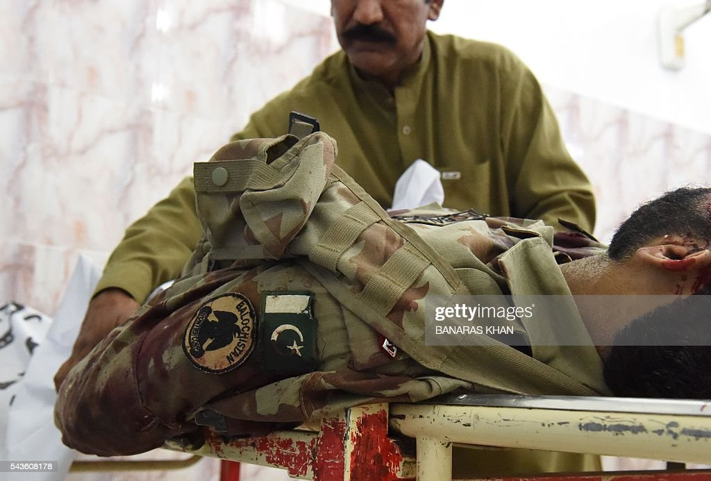 A Pakistani investigator checks the body of a paramilitary soldier who was killed during an attack by gunmen, at a hospital in Quetta on June 29, 2016. Gunmen on a motorcycle killed four paramilitary soldiers in the southwestern Pakistani city of Quetta on June 29, a day after four policemen were killed, officials said / AFP / BANARAS