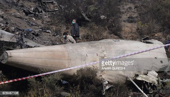 Pakistani investigators inspect the wreckage of the crashed PIA passenger plane Flight PK661 at the crash site in the village of Saddha Batolni in...