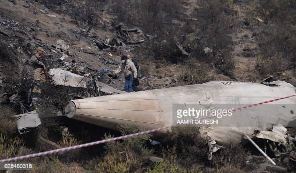 Pakistani investigators scan the wreckage of the crashed PIA passenger plane Flight PK661 at the crash site near the village of Saddha Batolni in the...