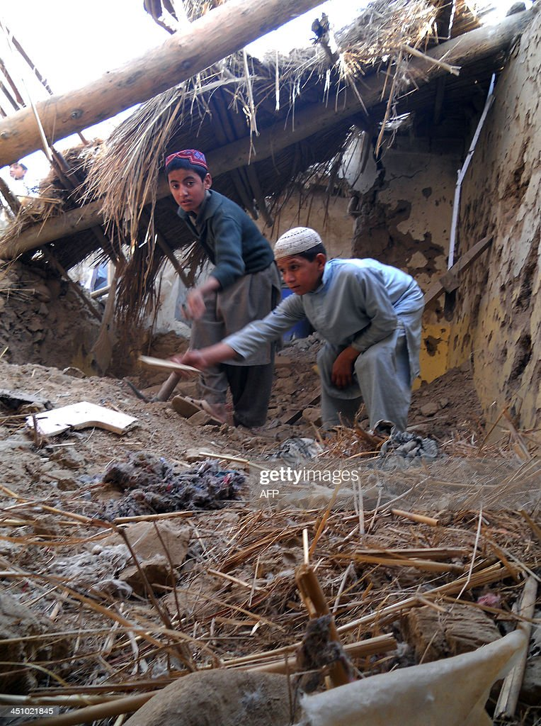 Pakistani Islamic students sift through rubble at a destroyed religious seminary belonging to the Haqqani network after a US drone strike in the...