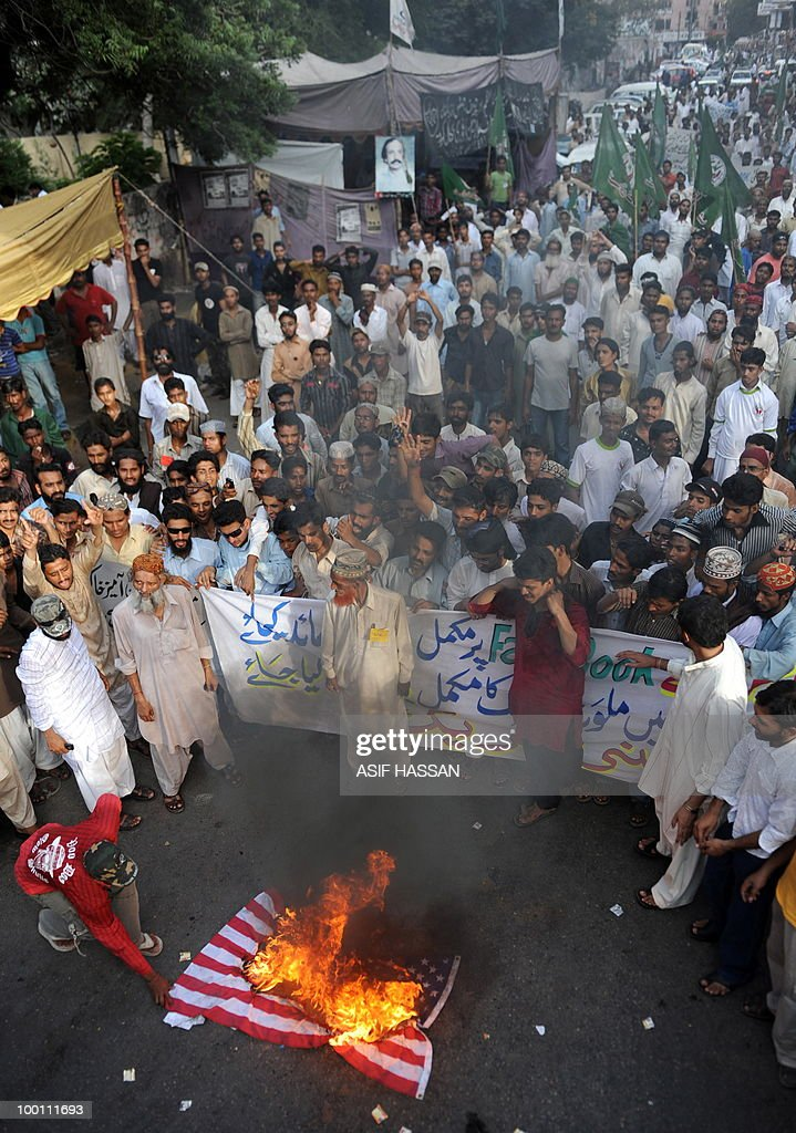 Pakistani Islamists gather beside a burning US national flag during a protest in Karachi on May 21, 2010, against the published caricatures of Prophet Mohammed on Facebook. Pakistani protesters shouted 'Death to Facebook', 'Death to America' and burnt US flags, venting growing anger over 'sacrilegious' caricatures of the Prophet Mohammed on the Internet. A Facebook user organised an 'Everyone Draw Mohammed Day' competition to promote 'freedom of expression', inspired by an American woman cartoonist, but sparked a major backlash in the conservative Muslim country of 170 million.