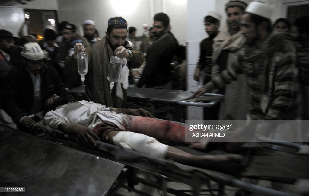 Pakistani Islamists transport an injured blast victim on a stretcher at a hospital in Peshawar on January 16, 2014. A bomb blast at an Islamic preaching centre in troubled northwest Pakistan killed at least six people and wounded more than 50, officials said.