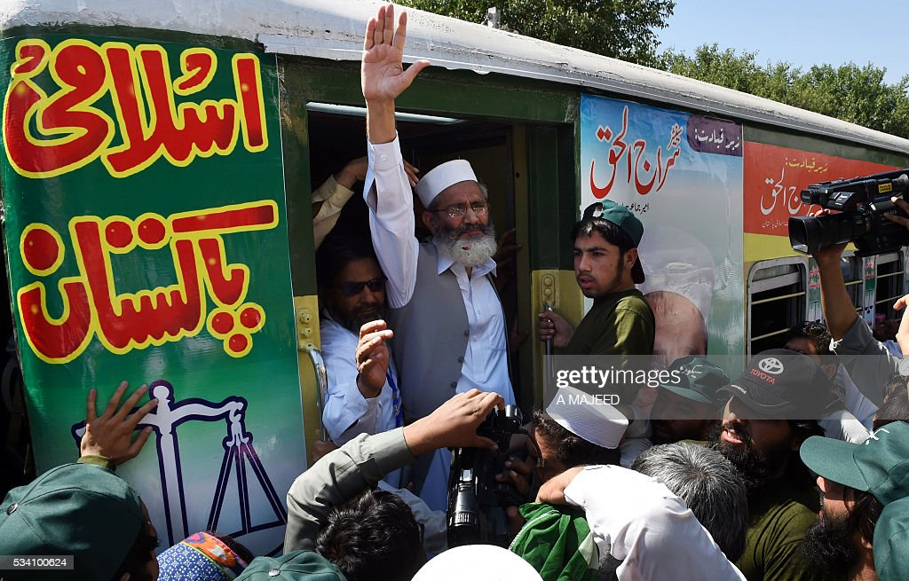 Pakistani Jamaat-i-Islami (JI) political and Islamic party leader Siraj-ul-Haq (C) waves to supporters at the start of a 'train march' at a railway station in Peshawar on May 25, 2016. The three-day 'Corruption Free Pakistan' train journey starts in Peshawar and is due to end in Karachi on May 27. / AFP / A