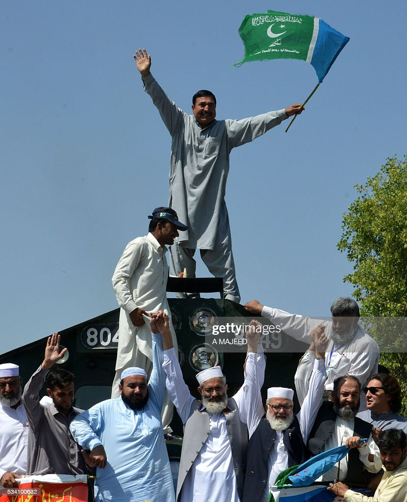 Pakistani Jamaat-i-Islami (JI) political and Islamic party leader Siraj-ul-Haq (C) and party leaders wave to supporters at the start of a 'train march' at a railway station in Peshawar on May 25, 2016. The three-day 'Corruption Free Pakistan' train journey starts in Peshawar and is due to end in Karachi on May 27. / AFP / A