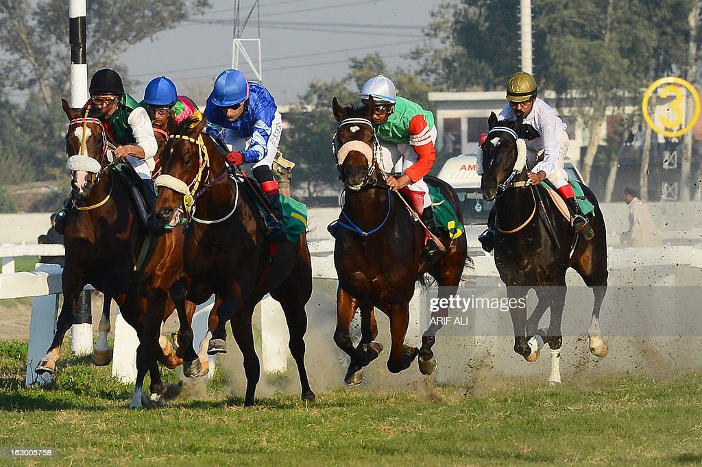 Pakistani jockey Amir Parviaz (C) rides his horse Denzaro at the annual Derby Horse Race in Lahore on March 3, 2013. Denzaro finished first in the race at the Lahore Race Club (LRC). AFP PHOTO/Arif ALI