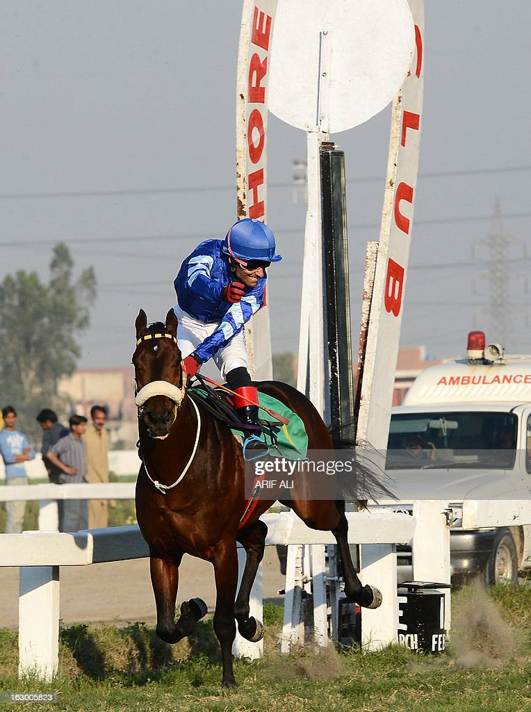 Pakistani jockey Amir Parviaz, riding Denzaro, gestures as he passes the winning post and celebrates his victory of the annual Derby Horse Race in Lahore on March 3, 2013. Parviaz on Denzaro finished first in the race at the Lahore Race Club (LRC). AFP PHOTO/Arif ALI