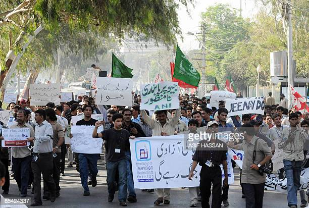 Pakistani journalists employee of private Geo news channel and political party activists shout slogans as they march during a protest in Karachi on...