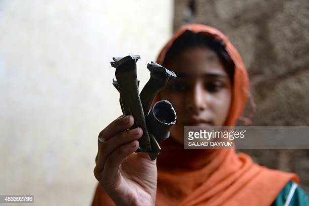 A Pakistani Kashmiri affected by cross border firing shows pieces of mortar shells at her home in Dhair Bazar Madarpur sector on the on the Line of...
