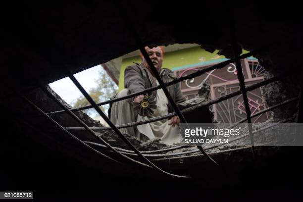 A Pakistani Kashmiri shows a mortar shell from his damaged house roof which was hit in crossborder shelling in the village of Peer Klanjer on the...
