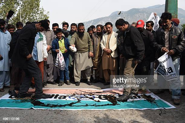 Pakistani Kashmiris step on a poster depicting the Indian flag as they take part in a protest against a visit by Indian Prime Minister Narendra Modi...