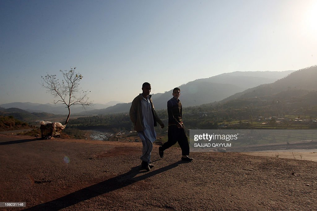 Pakistani Kashmiris walk on a road leading towards the town of Titrinot, some 30 kilometers north of Battal sector close of Pakistan-India border, on January 10, 2013. Pakistan on January 10 accused Indian troops of opening fire and killing a Pakistani soldier, the third deadly cross-border incident in days that threatens to escalate tensions in Kashmir. The Pakistan military said the incident happened in the Battal area of the disputed Himalayan region, where a ceasefire has held on heavily militarised Line of Control since 2003, despite violations on both sides. AFP PHOTO/Sajjad QAYYUM