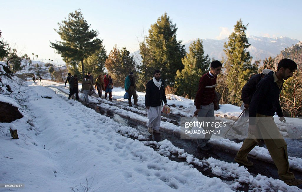 Pakistani Kashmiris walk through the snow in Muzaffarabad, the capital of Pakistani-administered Kashmir on February 6, 2013. Days of torrential rain have killed 34 people in Pakistan, mostly on the northwestern border with Afghanistan, officials said. AFP PHOTO/Sajjad QAYYUM