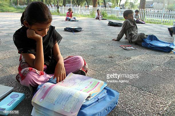 Pakistani kid reads a book while waiting for her teacher to start the lesson at a public park on 5 October 2013 inIslamabad Pakistan Volunteer...