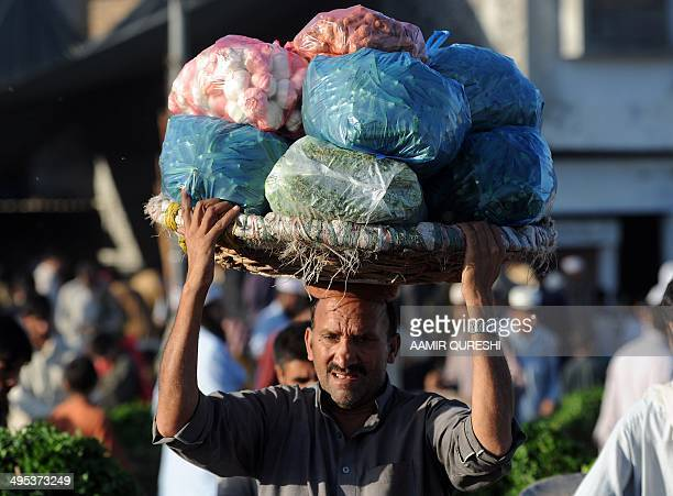 A Pakistani labourer carries a basket loaded with vegetables on his head at a fruit and vegetable market in Islamabad on June 3 2014 Pakistani...