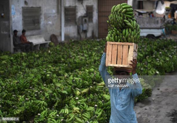 A Pakistani labourer carries a box of bananas at a fruit and vegetable market in Karachi on May 26 2017 Pakistan's economy expanded almost 53 percent...