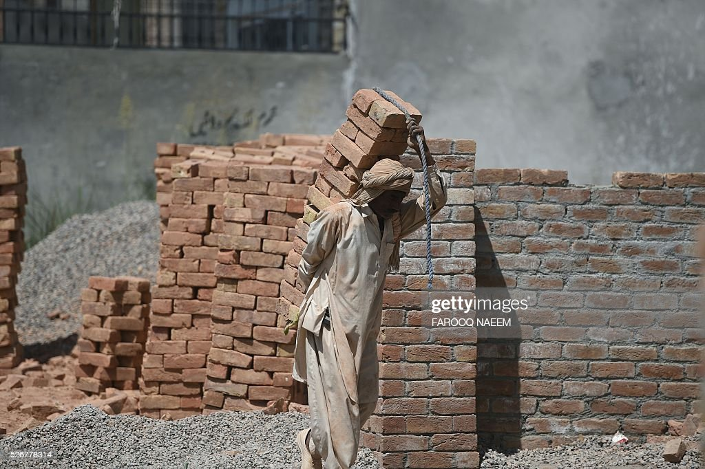 A Pakistani labourer carries bricks as he works on a construction site in Rawalpindi on May 1, 2016, on May Day. International Labour Day is marked annually on May 1. / AFP / FAROOQ