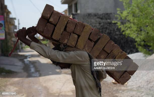 Pakistani labourer carries bricks on his back at a construction site at a residential area in Islamabad on March 29 2017 / AFP PHOTO / AAMIR QURESHI