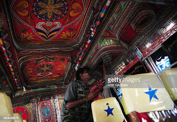 A Pakistani labourer decorates the interior of a passenger mini bus in Karachi on September 18 2013 Bus art has been very much in vogue in this port...