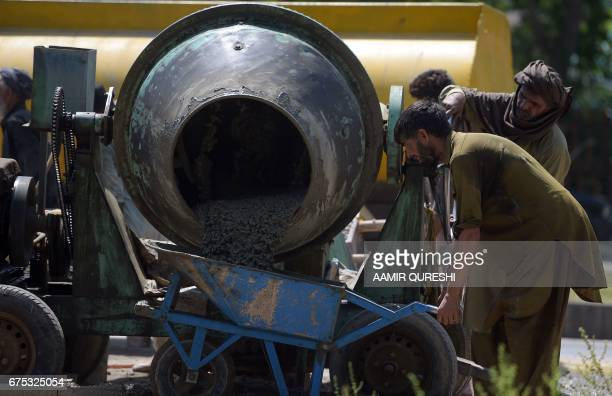 A Pakistani labourer fills a wheelbarrow with concrete from a mixer in Islamabad on May 1 on International Labour Day or May Day / AFP PHOTO / AAMIR...