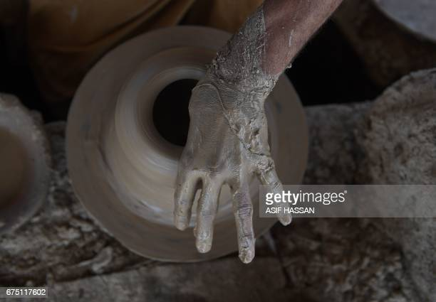 Pakistani labourer makes clay pots at a factory in Karachi on April 30 ahead of International Labour day / AFP PHOTO / ASIF HASSAN