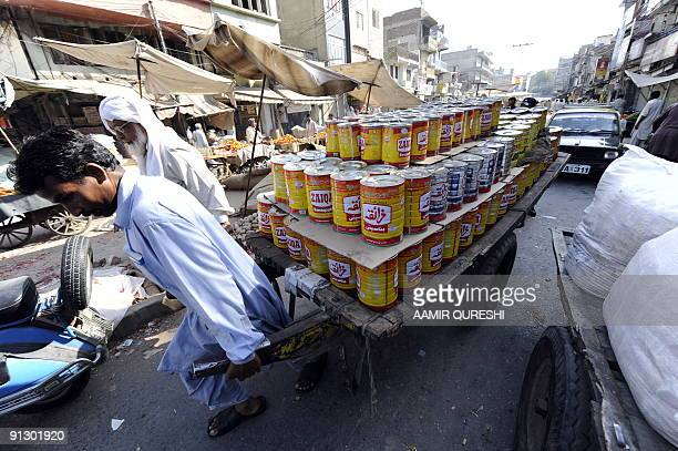 A Pakistani labourer pulls a cart laden with cooking oil through a main wholesale market in Rawalpindi on September 30 2009 Pakistan's central bank...