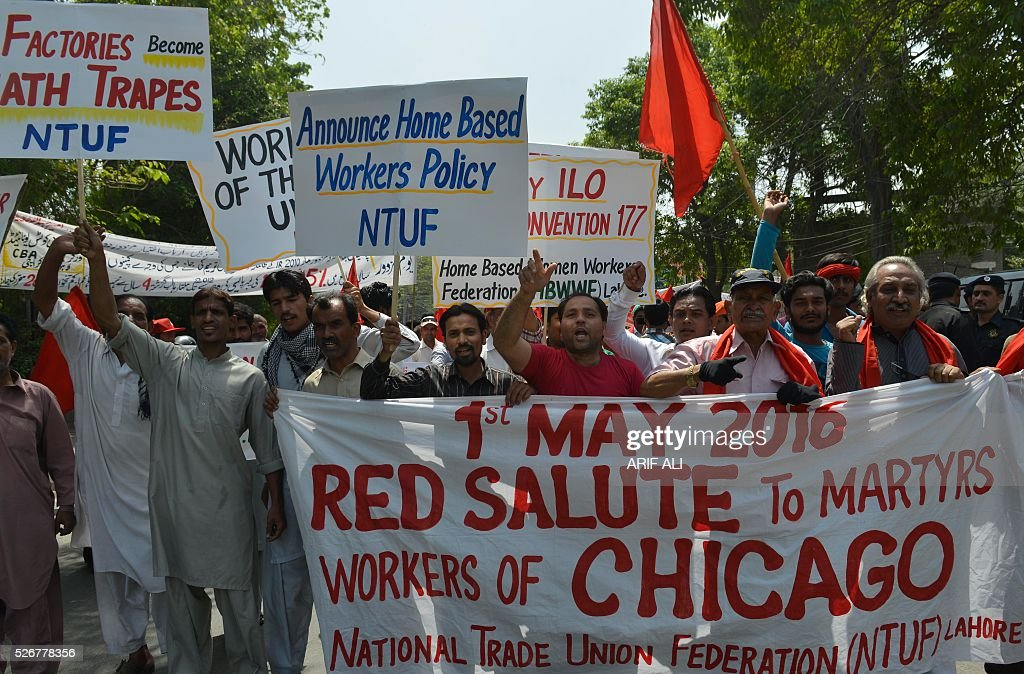 Pakistani labourer right activists shout slogans as they hold placards while marching in a rally in Lahore on May 1, 2016, on May Day. International Labour Day is marked annually on May 1. / AFP / ARIF ALI